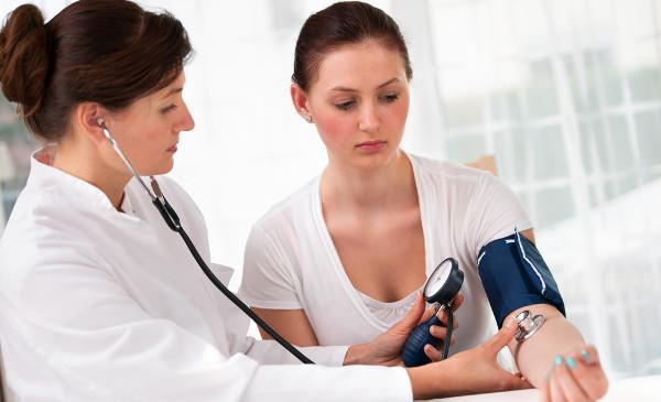 доктор меряет девушке давление