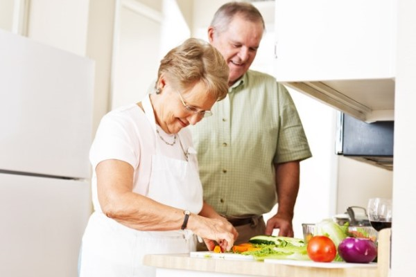 супруги готовят на кухне салат