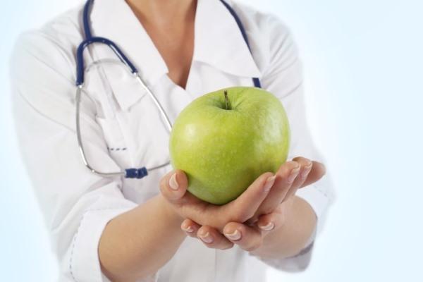 Доктор держит в руках зеленое яблоко