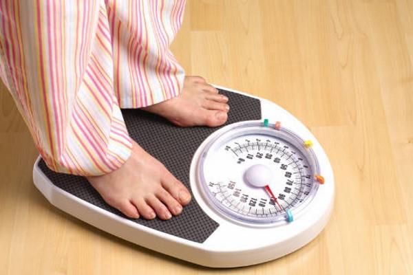 Избыточный вес, человек стоит на весах