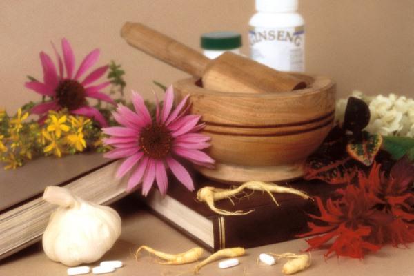 Цветы, травы, чеснок, книги, деревянная ступка, флаконы с лекарствами