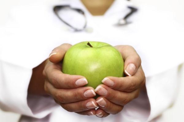 Врач держит в руках яблоко