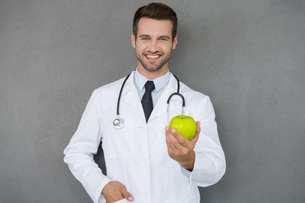 Доктор держит в руке зеленое яблоко