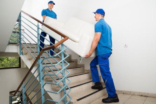 грузчики несут мебель по лестнице