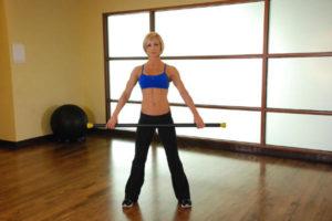 девушка выполняет упражнения с палкой