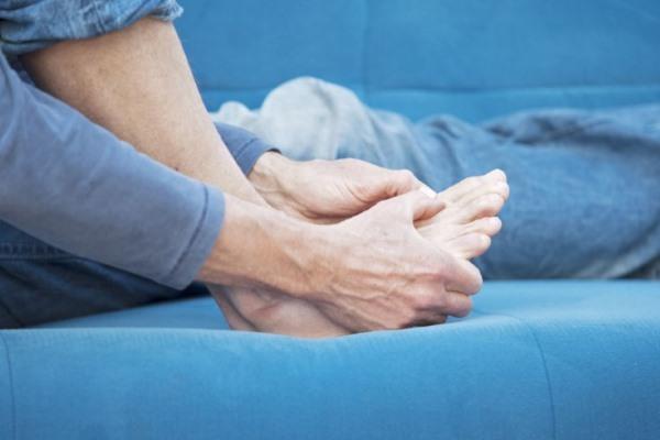 Артрит пальцев на ногах, человек держится за стопу