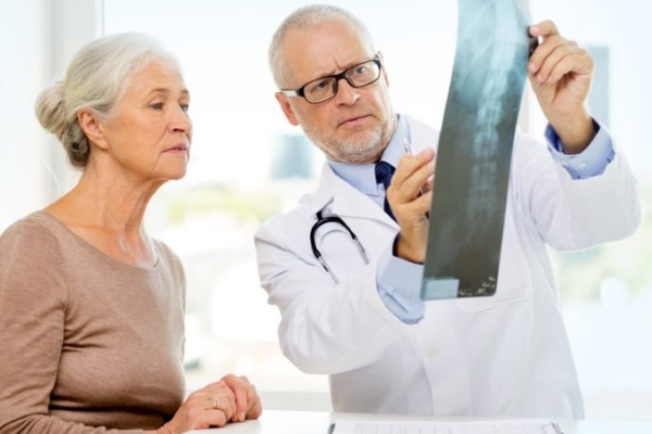 Врач и пациент смотрят рентгеновский снимок