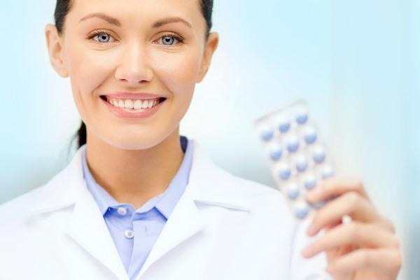 Доктор держит в руке таблетки