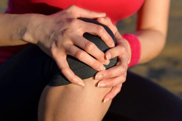 Женщина обхватила ладонями колено